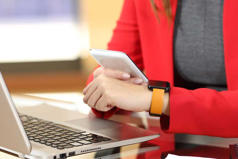 Person in Red Blazer with orange watch with computer and holding phone